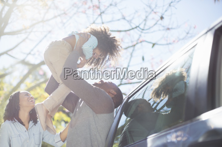 father lifting daughter overhead outside car