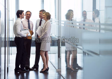 business people talking in office hallway