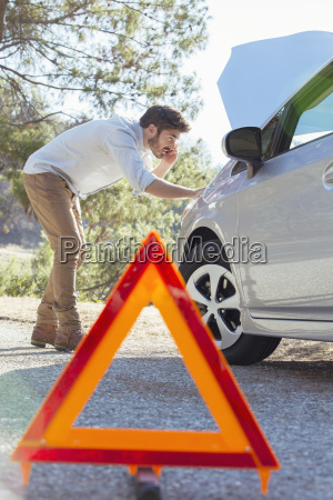 man at roadside checking car engine