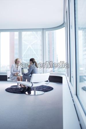 businesswomen talking in office lobby