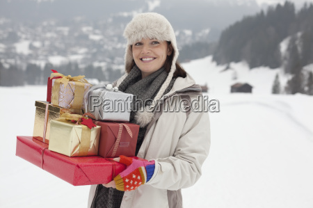 portrait of smiling woman carrying christmas