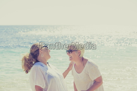 women laughing on sunny beach