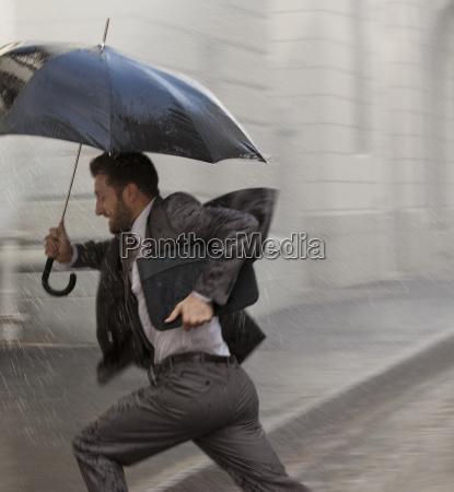 businessman with umbrella running in rain
