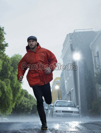 man in raincoat running in rain