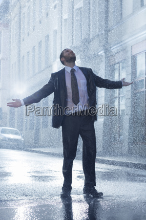 businessman standing with arms outstretched in