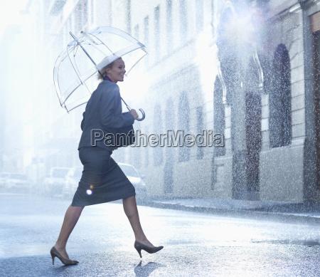 happy businesswoman with umbrella walking across