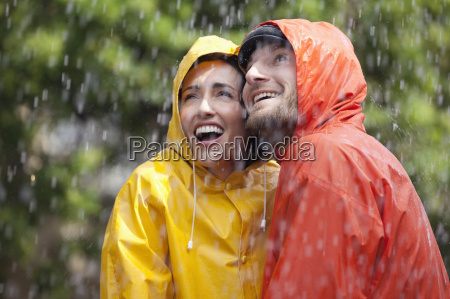 happy couple in raincoats looking up
