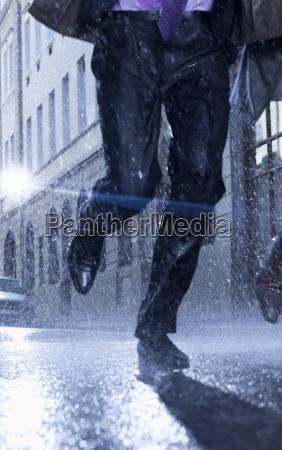 businessman running in rainy street