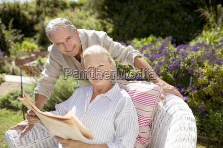 senior couple reading newspaper in garden
