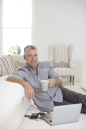 senior man using laptop on living