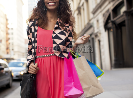 woman carrying shopping bags on city