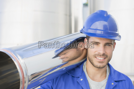 portrait of smiling worker carrying stainless