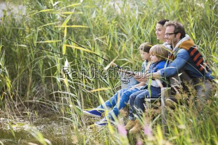 family fishing together in tall grass