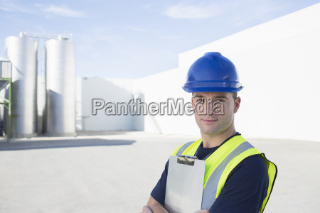 portrait of confident worker with clipboard
