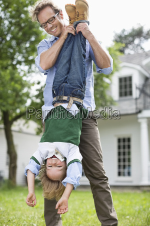 father and son playing together outdoors