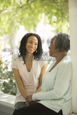 mother and daughter talking on porch