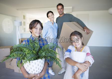 portrait of smiling family holding belongings