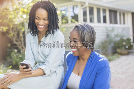 smiling mother and daughter text messaging