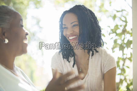mother and daughter laughing outdoors