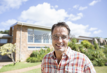 portrait of smiling man outside house