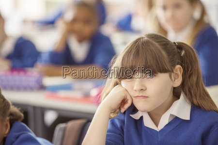 elementary schoolgirl looking bored during lesson