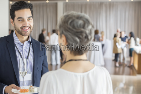 businessman talking to businesswoman during reception