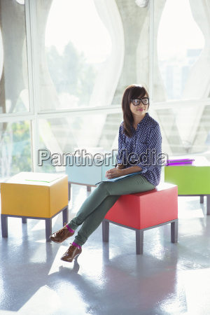creative businesswoman waiting on colorful stool