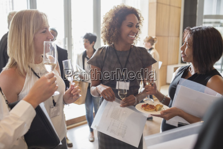 businesswomen holding flutes of champagne and