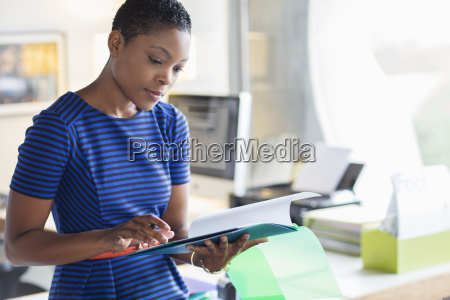 serious businesswoman reviewing paperwork in office