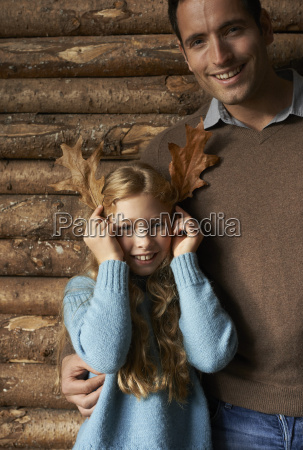 girl using leaves as antlers with