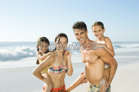 parents carrying daughters piggyback on beach