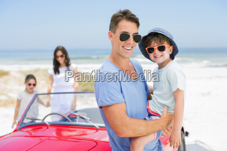 father and son smiling near convertible
