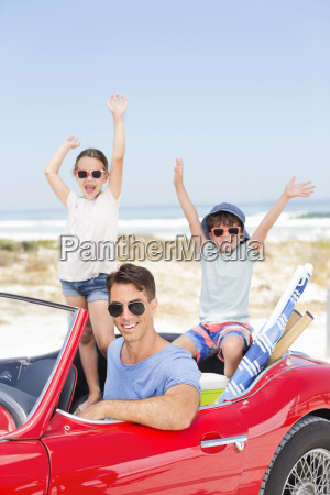 father and children in convertible at