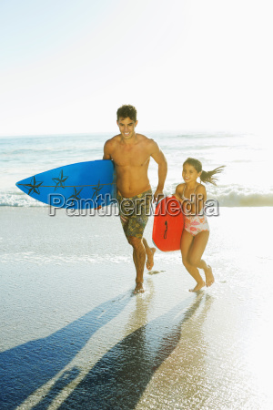 father and daughter carrying surfboard and