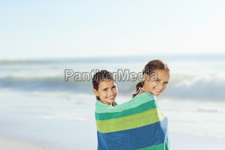 girls wrapped in towel on beach