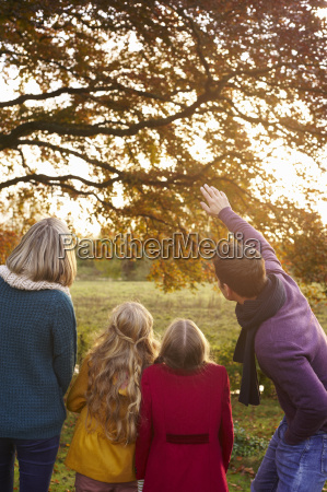 family admiring autumn leaves in tree