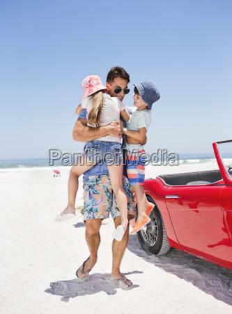 father hugging children on beach next