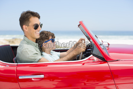 father and son driving convertible at