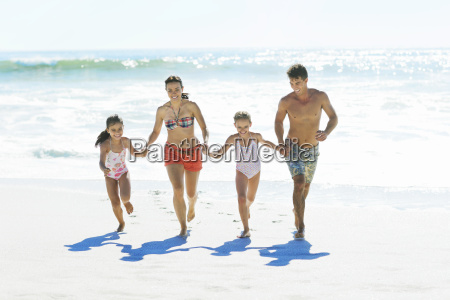 family holding hands and running on