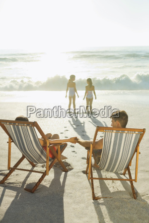 parents watching daughters on beach at