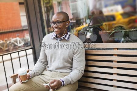 man listening to earphones on city