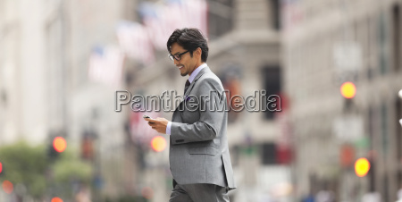 businessman using cell phone on city
