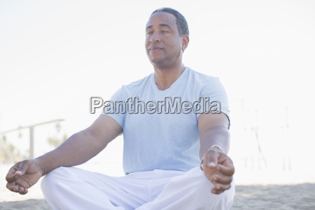 serene senior man meditating in lotus