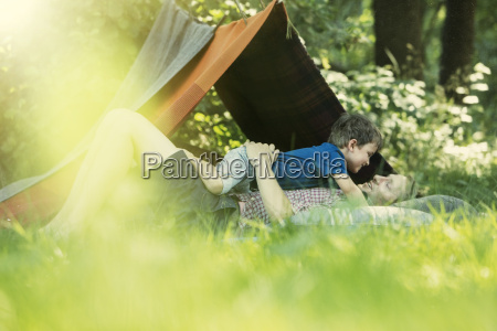 father and son laying in grass