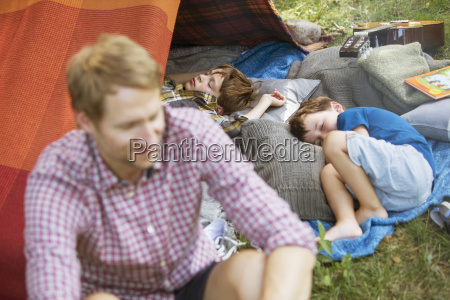 father sitting with sleeping sons at