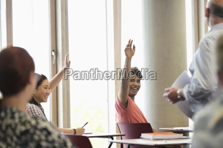 smiling university students raising hands at
