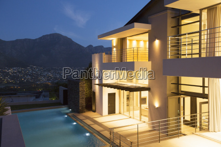 modern house with swimming pool illuminated