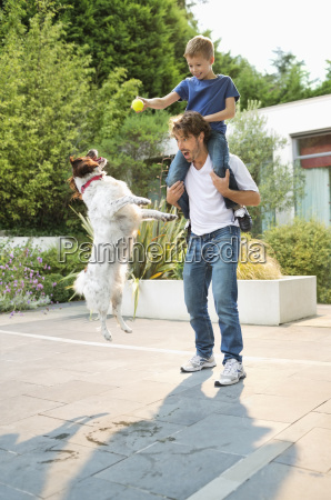 father and son playing with dog