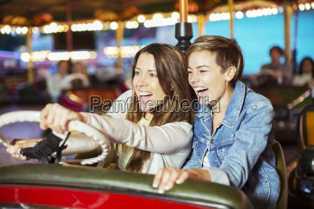 two cheerful women on bumper car
