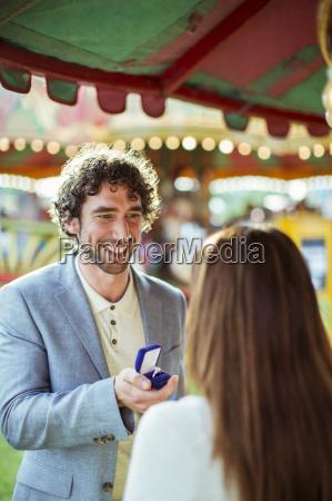 man proposing to girlfriend in amusement